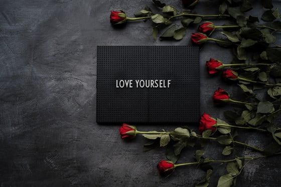 nápis láska na čiernej krabici a ruže