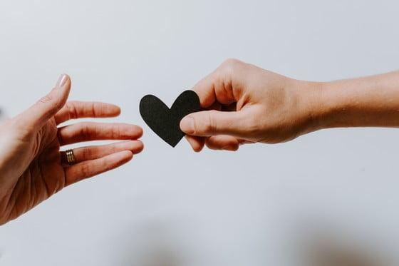 žena podáva čierne papierové srdce mužovi