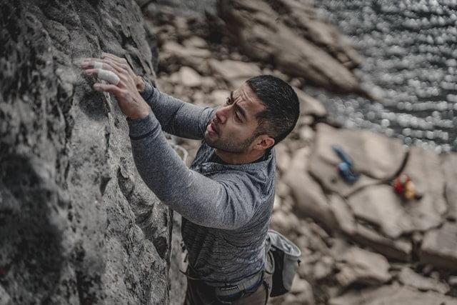 muž ktorý sa šplhá po skale