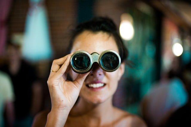 žena ktorá sa pozerá cez ďalekohľad