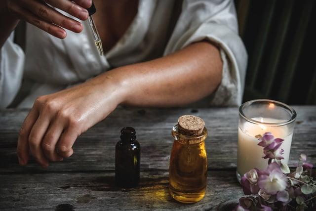 žena kvapkajúca olej na ruku