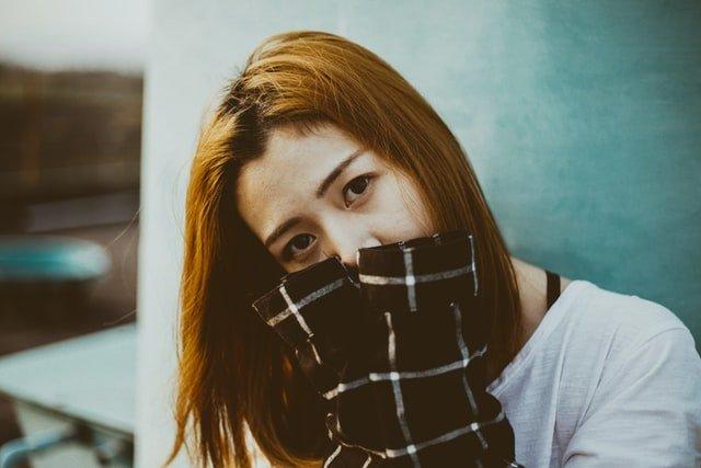 hanblivá žena si kryje tvár