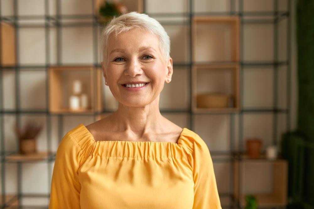 šťastná staršia žena vo žlto-oranžovom